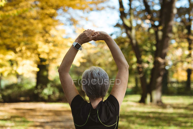 Rear view of senior woman practicing yoga in a park on a sunny day — Stock Photo