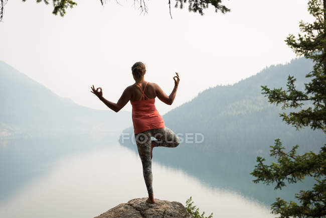 Fit woman balancing on one leg on the edge of a rock at the time of dawn — Stock Photo