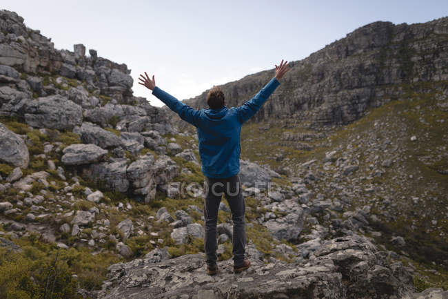 Rear view of hiker standing on rock with raised hands — Stock Photo