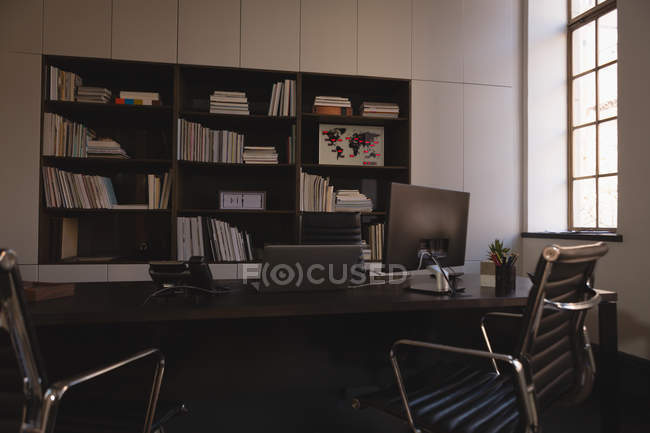 Modern Bookcase And Desk With Chairs In Office Desktop Pc