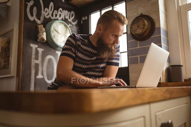 Hombre usando el ordenador portátil, mientras que el revestimiento en el mostrador de cocina en cocina - foto de stock