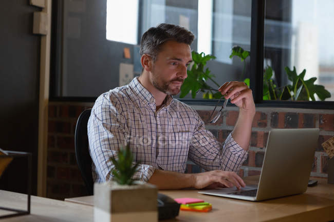 Business executive working on laptop at desk in office. — Stock Photo