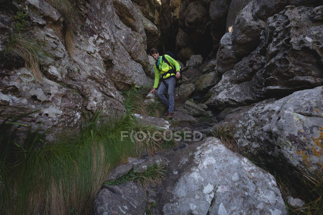 Hiker walking down on rocks with backpack — Stock Photo