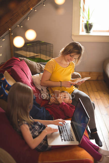Family on sofa using multimedia devices at home — Stock Photo