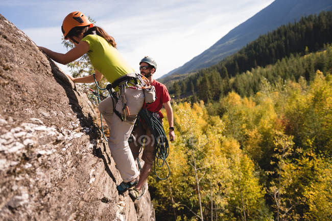 Determined rock climbers reaching on the cliff top — Stock Photo