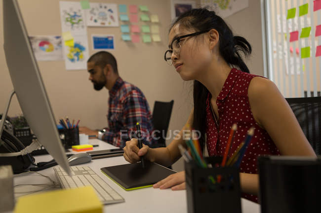 Female graphic designer using graphics tablet at desk in office — Stock Photo