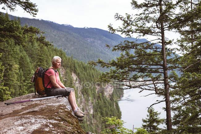 Vue latérale de la femme mûre se détendre sur le rocher et regarder la vue — Photo de stock