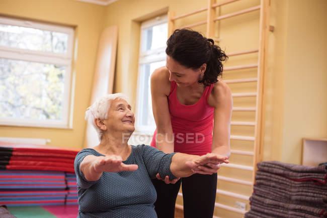 Terapeuta femenina que asiste a una mujer mayor con ejercicio de manos en un hogar de ancianos - foto de stock