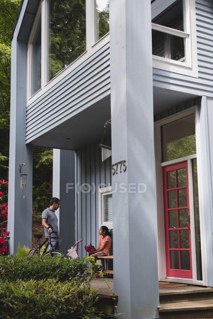 Father and daughter interacting with each other in the porch — Stock Photo