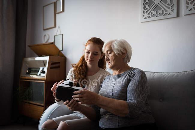 Enkelin, die Unterstützung der Großmutter mit virtual-Reality-Kopfhörer zu Hause — Stockfoto