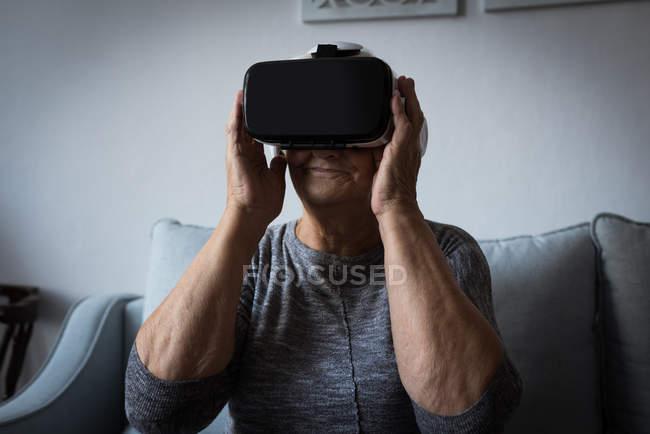 Старші жінки за допомогою віртуальної реальності гарнітуру у вітальні на дому — стокове фото