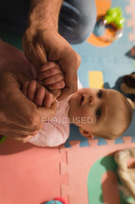 Primo piano delle mani del padre che giocano con il bambino a casa . — Foto stock