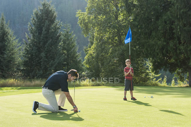 Father and son playing golf in the course — Stock Photo