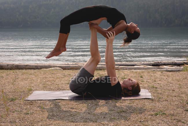 Couple sportif pratiquant l'acro yoga près de la côte par une journée ensoleillée — Photo de stock