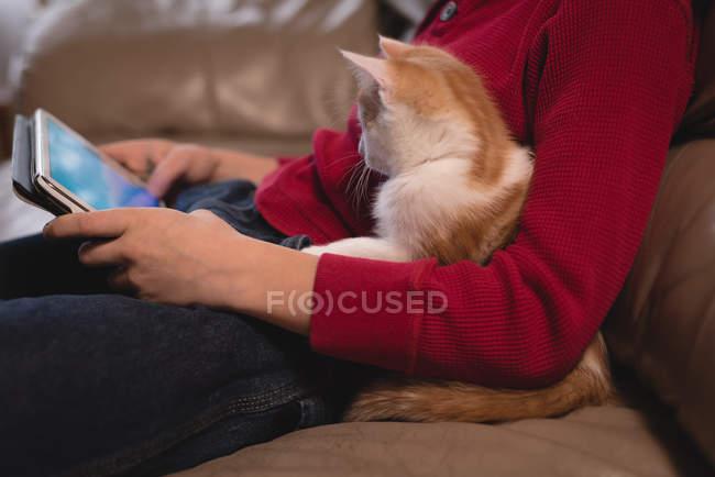 Мальчик использует цифровой планшет в гостиной со своим котом дома — стоковое фото