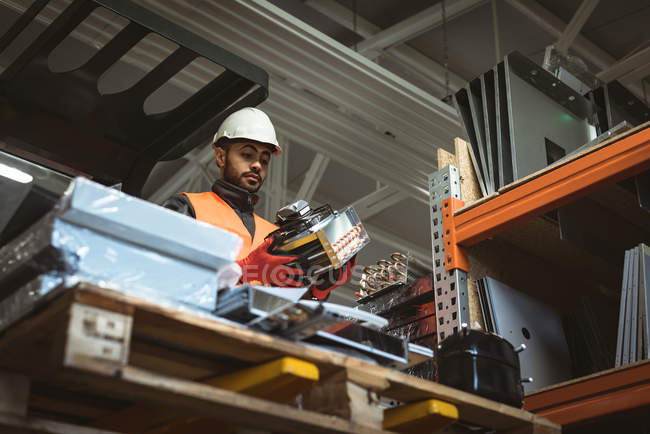 Male worker checking machine part in factory — Stock Photo