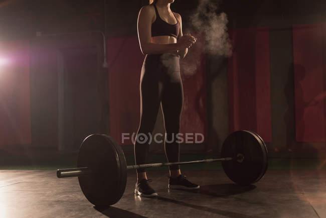 Femme se frottant la poudre sur place avant l'entraînement d'haltères en salle de gym — Photo de stock