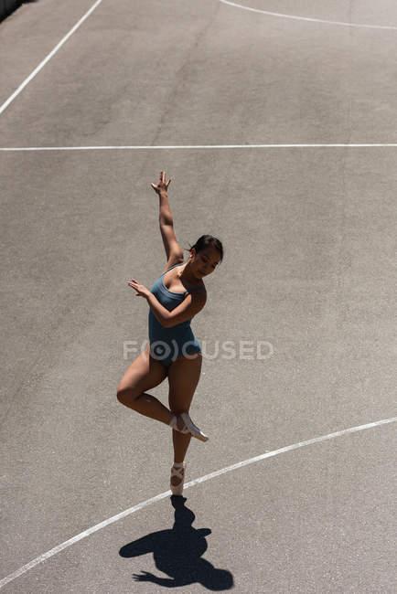 Молодая балетная танцовщица танцует на баскетбольной площадке — стоковое фото