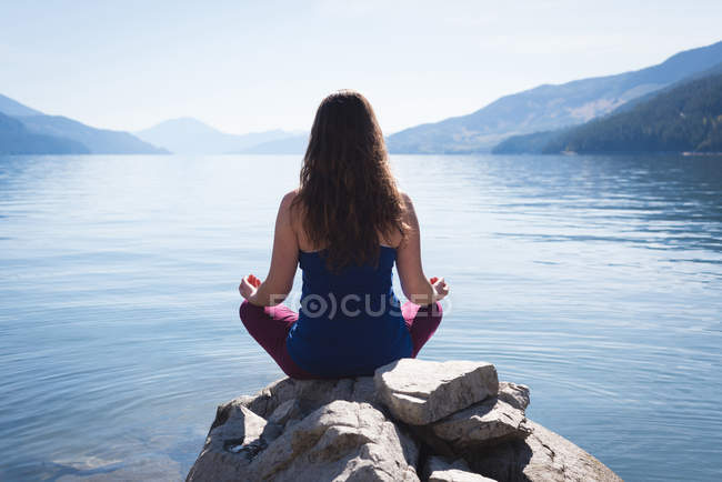 Woman practicing yoga on rock near sea side — Stock Photo