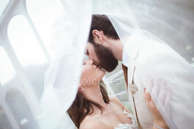 Gros plan de la mariée et le marié baiser sous le voile — Photo de stock