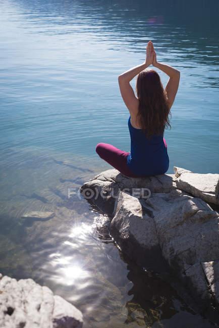Woman practicing yoga on rock near sea side — Stock Photo