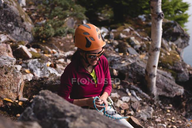 Женщина-туристка готовится подняться на скалистую гору возле озера — стоковое фото