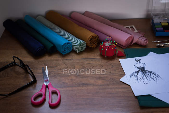 Fabric and design sketch on table in design studio. — Stock Photo