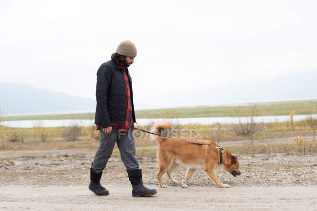 Man and his pet dog walking on empty path — Stock Photo