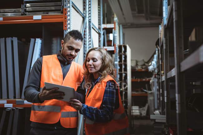 Zwei Arbeiter diskutieren in Fabrik über digitales Tablet — Stockfoto