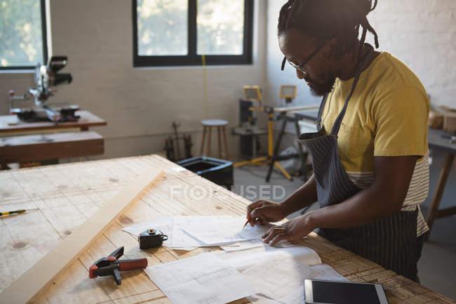 Carpinteiro trabalhando à mesa em oficina — Fotografia de Stock