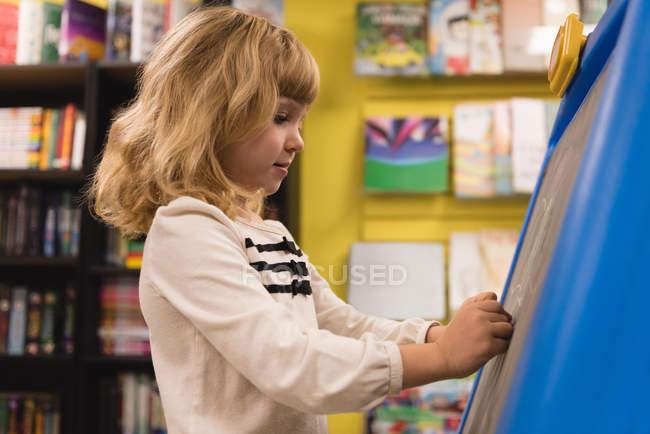 Fille écriture sur tableau noir dans la librairie — Photo de stock