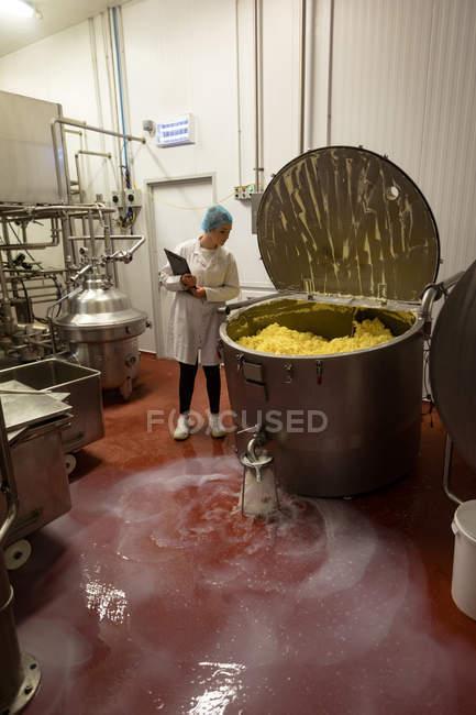 Travailleuse surveillant la pâte dans une énorme machine dans l'usine alimentaire — Photo de stock