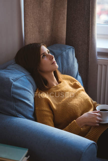 Young woman relaxing on sofa holding a cup of coffee during daytime at home — Stock Photo