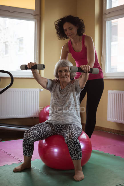 Female therapist assisting senior woman with dumbbells in nursing home — Stock Photo