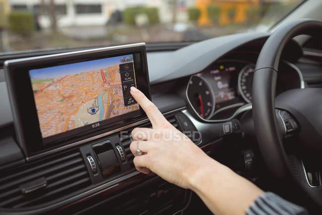 Primer plano de la mujer ejecutiva utilizando la navegación en un coche - foto de stock