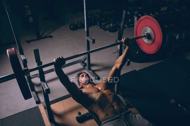 Overhead de hombre musculoso haciendo ejercicio con barra en el gimnasio - foto de stock