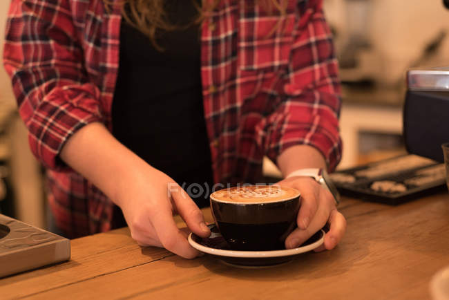 Mid section of female barista serving coffee at counter in cafe — Stock Photo