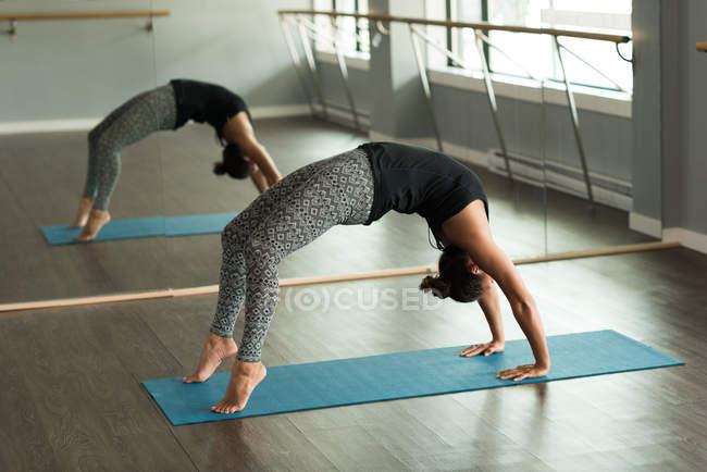 Woman practicing yoga on exercise mat in fitness studio. — Stock Photo