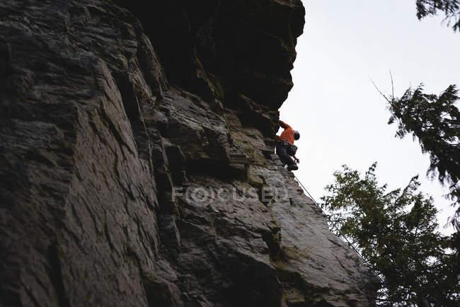 Vista de baixo ângulo do alpinista escalando o penhasco rochoso — Fotografia de Stock