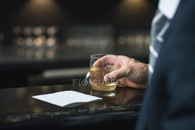 Обрезанный образ бизнесмена за бокалом виски у стойки отеля — стоковое фото