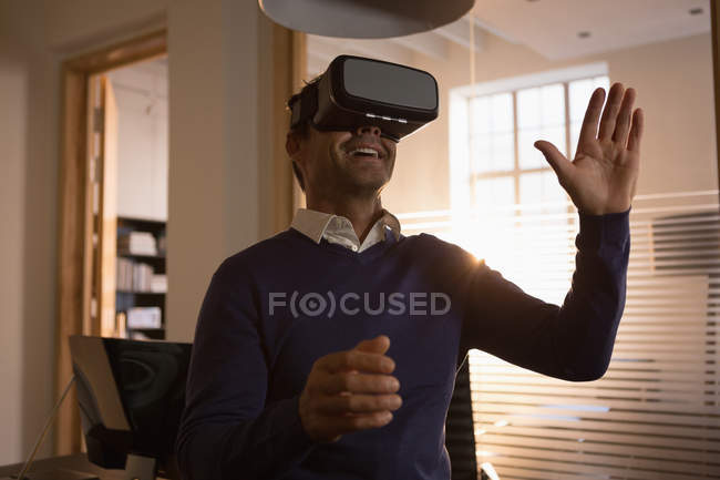 Hombre de negocios sonriente usando auriculares de realidad virtual en la oficina . - foto de stock