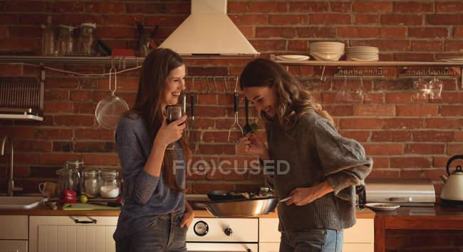 Счастливые друзья с вином на кухне дома — стоковое фото