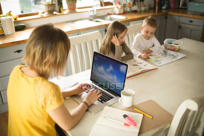 Los hermanos dibujo mientras que la madre que trabaja en el ordenador portátil en la cocina en casa - foto de stock