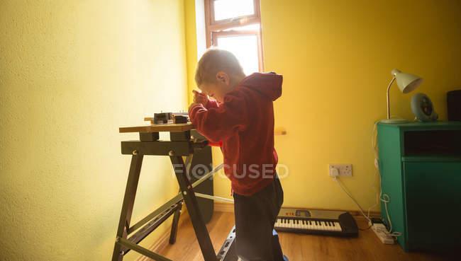 Мальчик с помощью инструмента на деревянной доске дома — стоковое фото