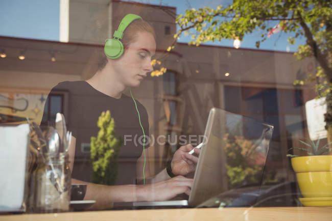 Mann hört Musik über Kopfhörer, während er Handy und Laptop im Café benutzt — Stockfoto