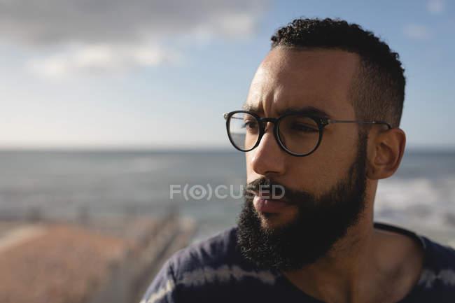 Primo piano uomo in piedi vicino alla spiaggia nella giornata di sole — Foto stock