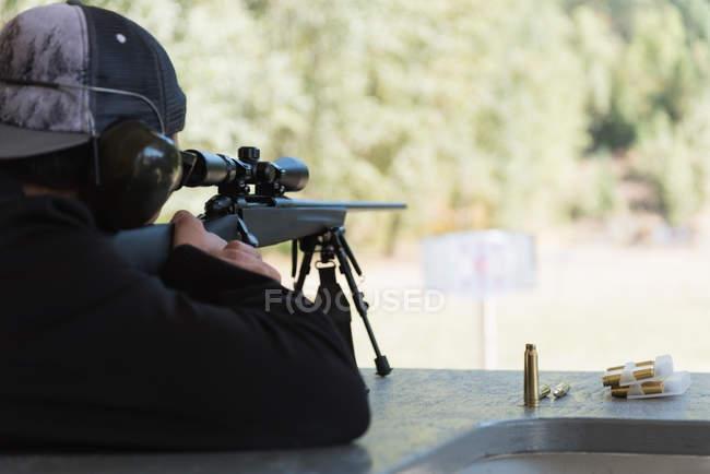 Vista traseira do homem apontando o rifle sniper no alvo no tiro ao alvo — Fotografia de Stock