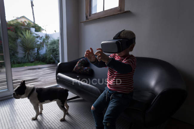 Boy using virtual reality headset in living room at home. — Stock Photo