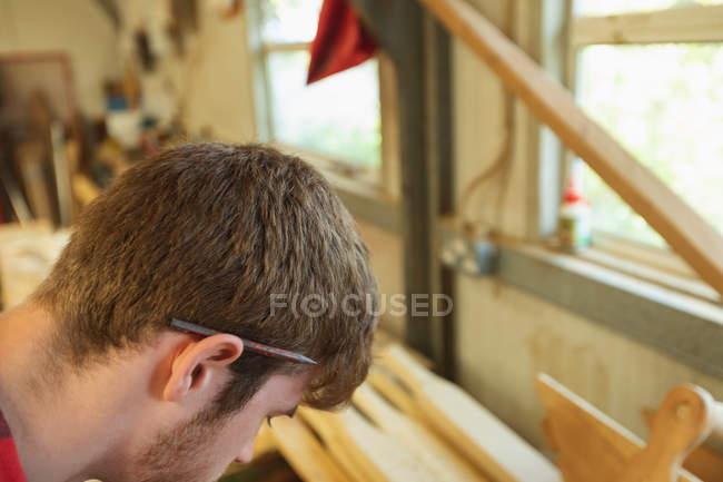 Joven carpintero masculino trabajando en taller - foto de stock