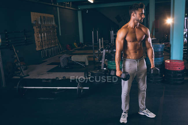 Muscular man exercising with dumbbells in fitness studio — Stock Photo